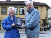 Karin Hansen og Lasse Solberg med kalenderen, mens Per Kristian Hansen står i vinduet (2010)